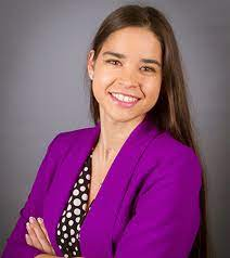 Shailana Dunn Wall wears a purple jacket and a white and brown polka dot shirt and smiels with her arms crossed.