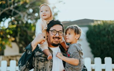 Father with glasses and beard has a baby on his shoulder and a three year old child in his arms. He wears a whitewashed jean jacket and a white tshirt.